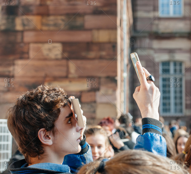 Strasbourg, France - March 20, 2015: Boy with protective eyewear taking a photo of solar eclipse with his smartphone