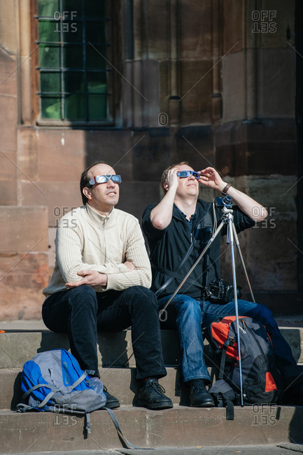 Strasbourg, France - March 20, 2015: Two men seated on steps watching a solar eclipse with protective eyewear