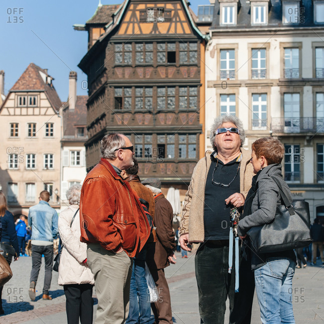 Strasbourg, France - March 20, 2015: People on the streets of Strasbourg watching a rare solar eclipse