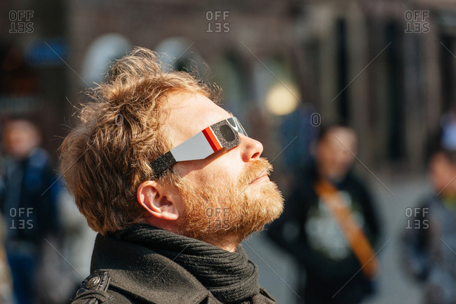 Strasbourg, France - March 20, 2015: Profile view of man watching solar eclipse with protective glasses