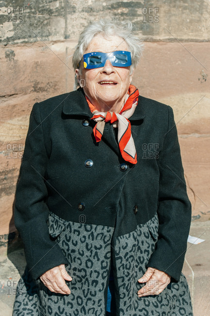 Strasbourg, France - March 20, 2015: Smiling senior woman viewing solar eclipse through protective glasses