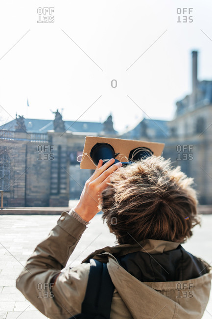 Back view of woman watching a solar eclipse through binoculars