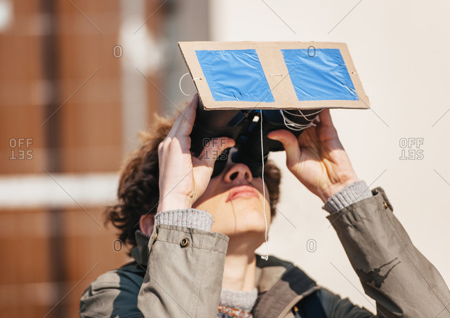 Strasbourg, France - March 20, 2015: Woman with adapted binoculars watches a rare solar eclipse