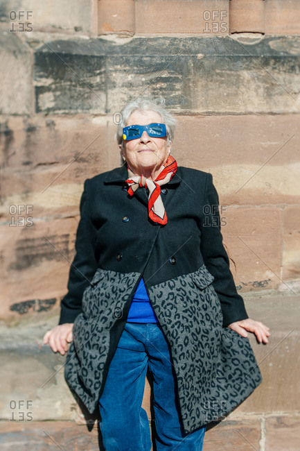 Strasbourg, France - March 20, 2015: Impressed senior woman leans against a wall to watch solar eclipse with protective glasses