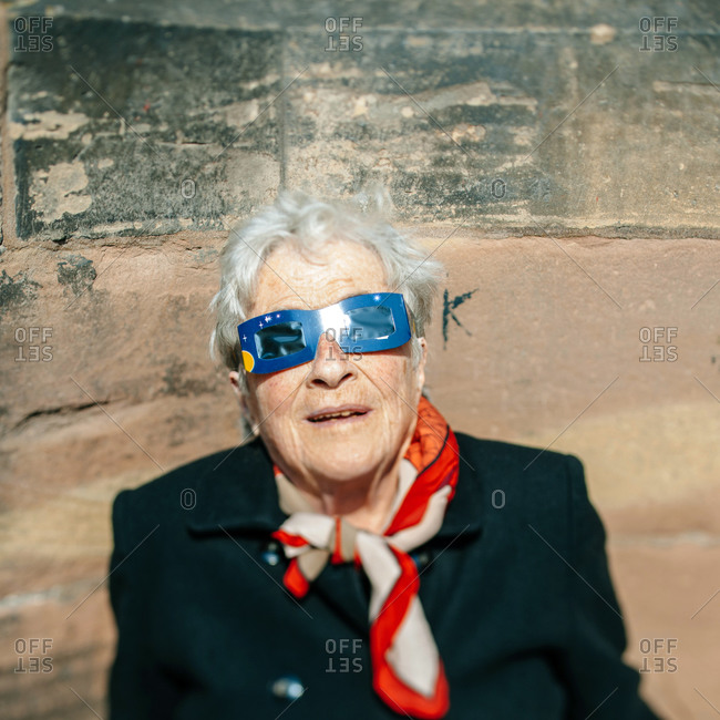 Strasbourg, France - March 20, 2015: Elderly woman watches a solar eclipse through protective glasses