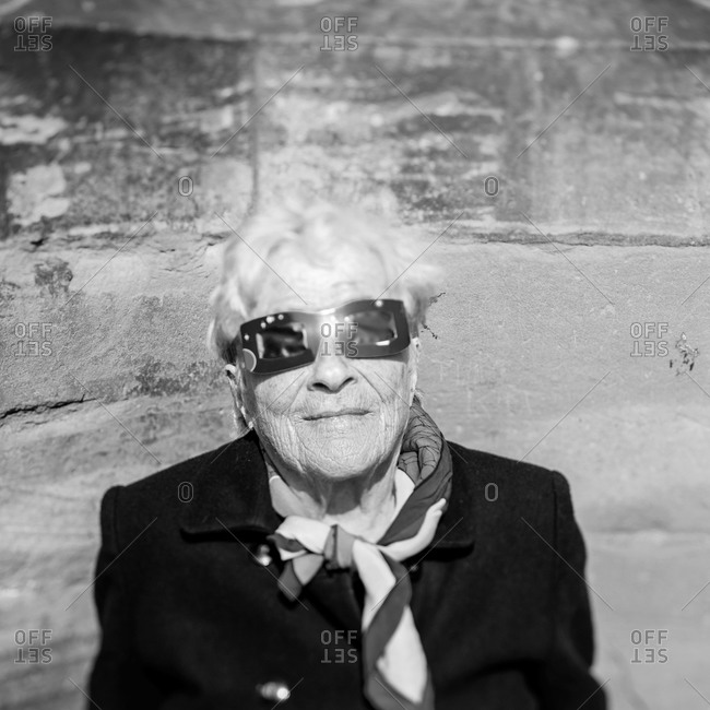 Strasbourg, France - March 20, 2015: Portrait of a senior woman wearing protective glasses to watch a solar eclipse