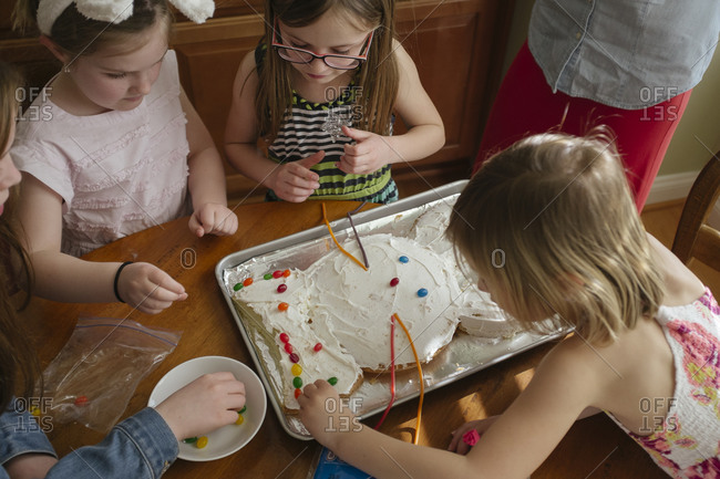 Children working together to decorate a bunny cake