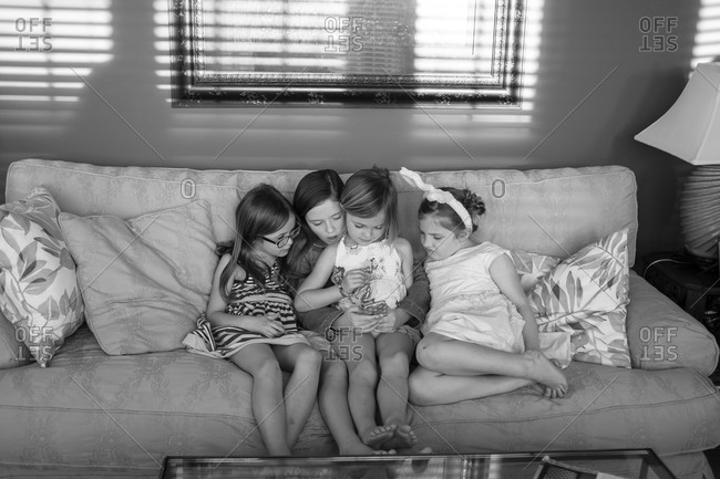 Four girls surround a mobile device