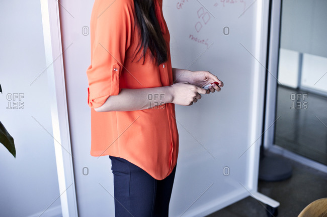Brunette woman holding a marker at a whiteboard