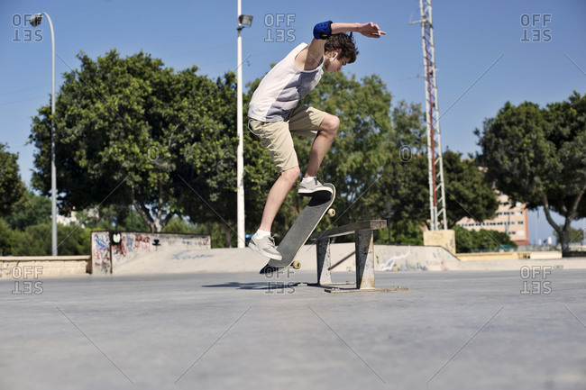 Teenaged boy doing tricks at a skate park