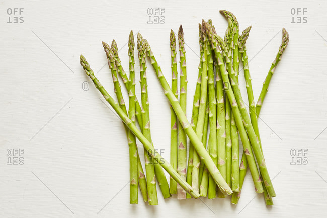 Raw asparagus tips on white background