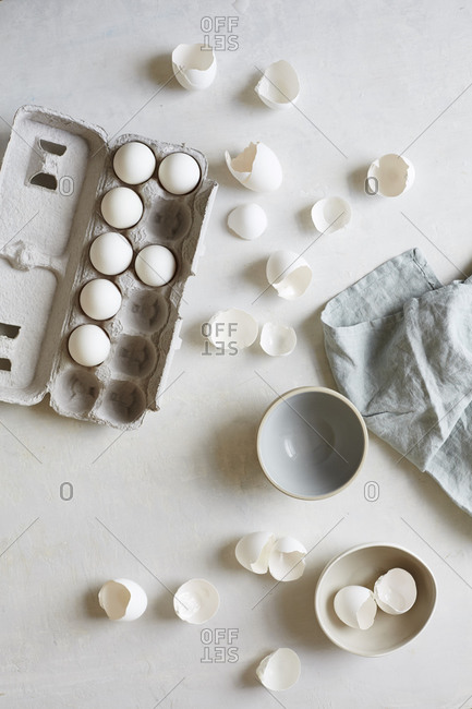 Eggs and cracked eggshells by bowls