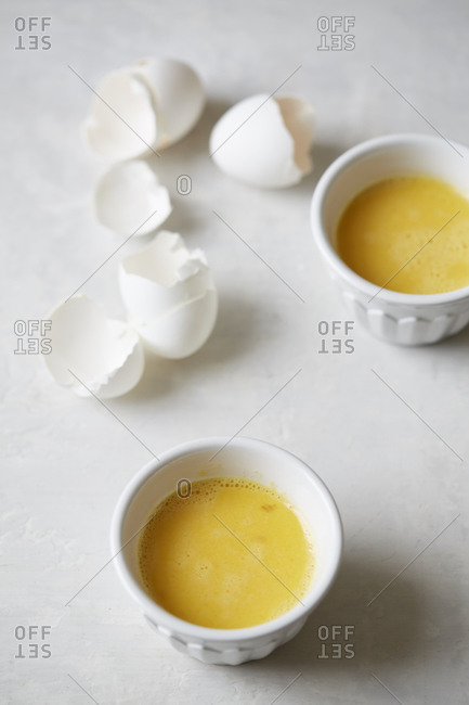 Egg shells and whisked eggs in bowl