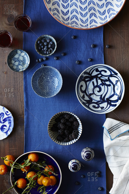 Whole oranges and berries in dishes on table