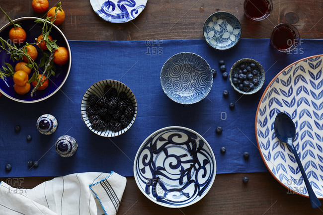 Oranges and berries in dishes on table