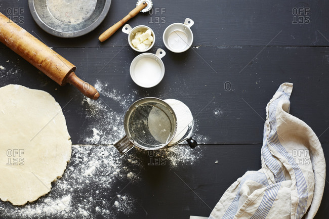 Rolled out raw pie dough and pie making supplies