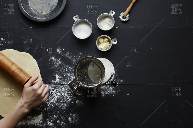 Person rolling pie dough by pie making supplies