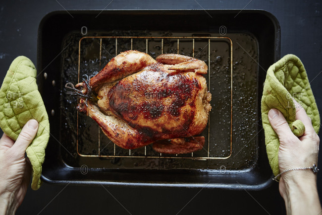 Person holding pan with whole baked chicken
