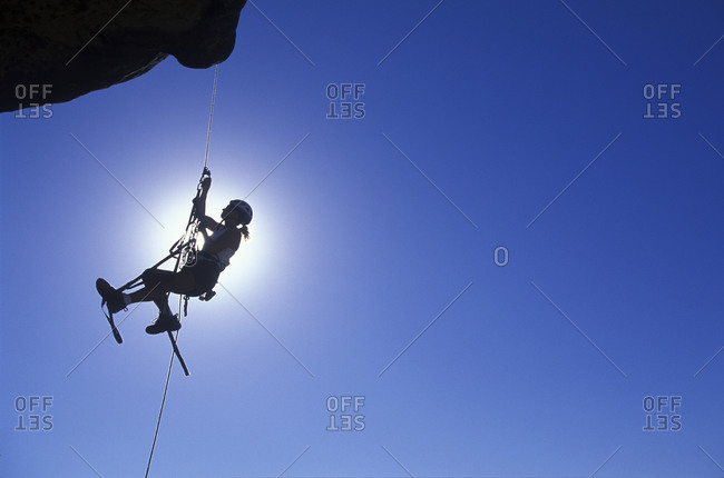 A climber dangles in midair as she rappels from the summit of a rock spire