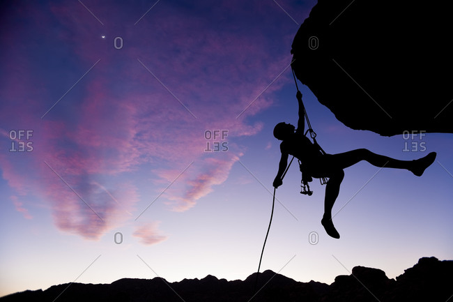Silhouette of a climber hanging from rock face at sunset