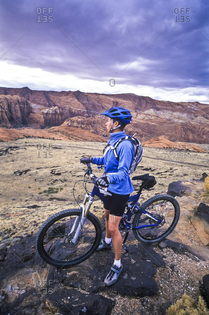 Female mountain biker rests and enjoys the view from a cliff edge