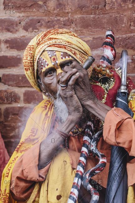 Kathmandu, Nepal - July 7, 2011: Nepalese holy man smoking a pipe