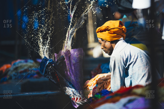 Mumbai, India - January 21, 2015: Man in Mumbai cleaning clothes