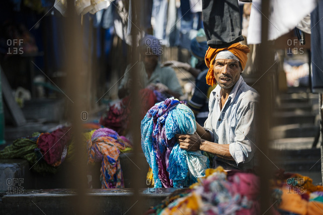 Mumbai, India - January 21, 2015: Man washing laundry in Mumbai