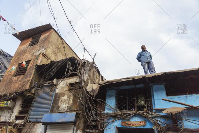 Mumbai, India - February 7, 2015: Man standing on roof in Mumbai slum