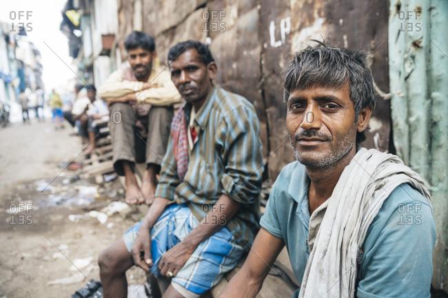 Mumbai, India - February 7, 2015: Workers at rest in Mumbai slum