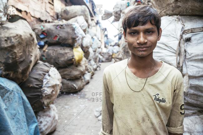 Mumbai, India - February 7, 2015: Portrait of teen in trash filled Mumbai street