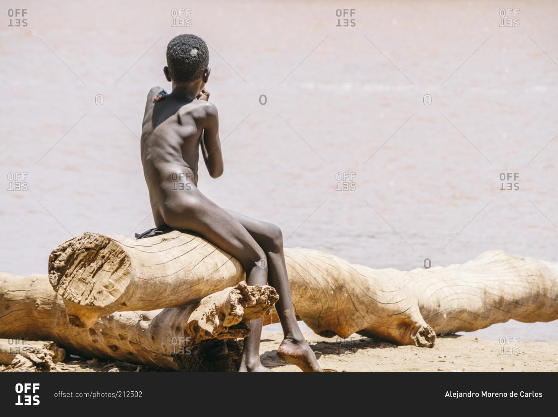 ethiopian boy sitting naked on log stock photo   offset