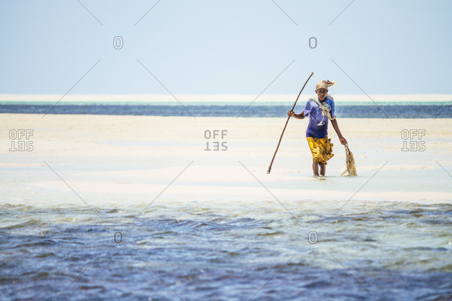 Vilanculos, Mozambique - October 8, 2014: Woman in shallow water crab hunting in Mozambique