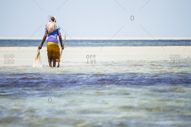 Woman on Mozambique beach crab hunting