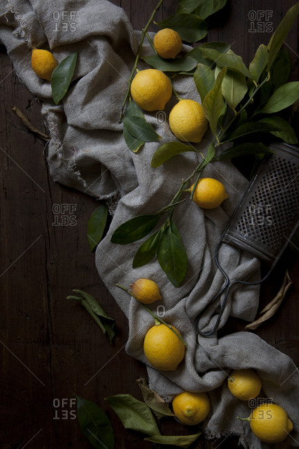 A group of fresh lemons with leaves on a wooden table with a grater