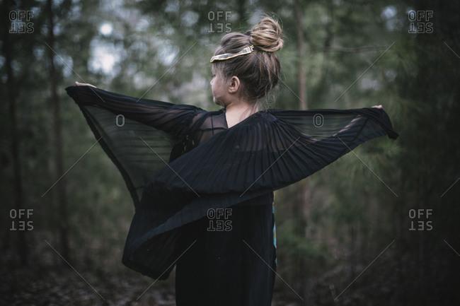 A little girl walks through the woods in a black dress