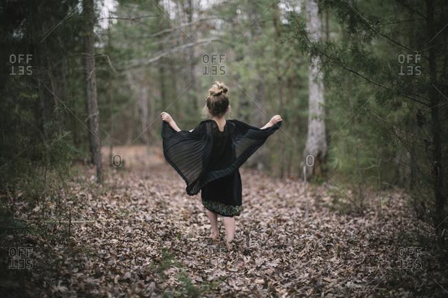 A little girl roams through the woods in a black dress