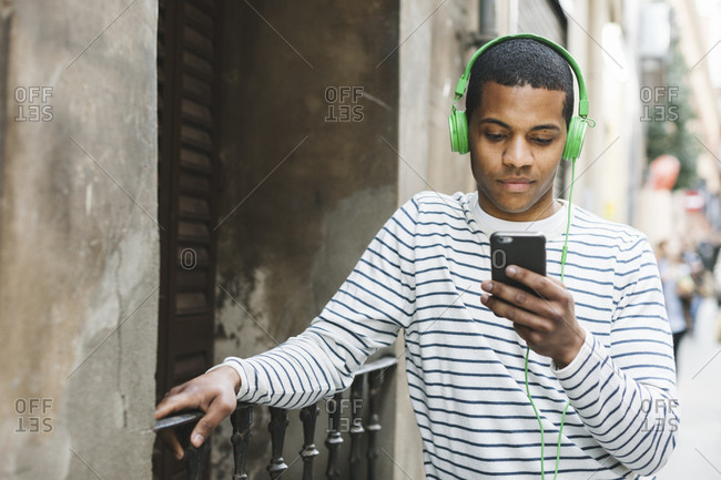 Young man listening to  music with headphones on street