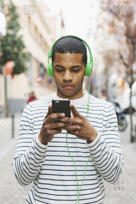 Young man listening to  music with green headphones on street