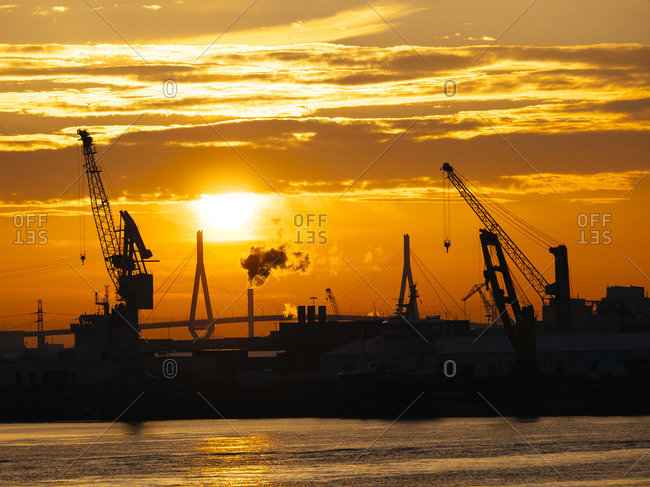 Silhouettes of harbor cranes at sunset with the Koehlbrand bridge