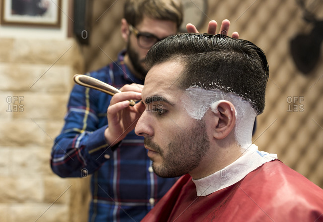 Hairdresser shaving sides of a young man's hair in a barbershop