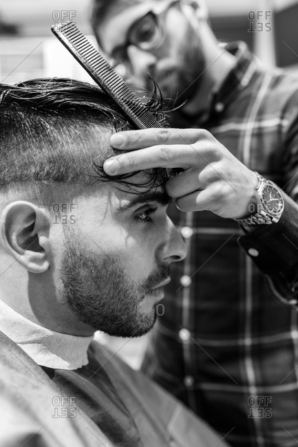 Barber cutting young man's hair in a barbershop