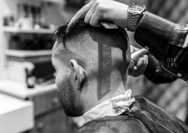 Hairdresser shaving young man's head in a barbershop
