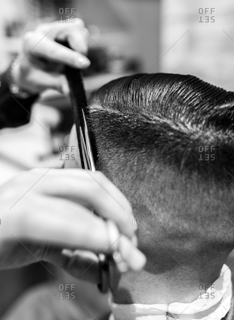 Close up of a young man getting his hair trimmed in a barbershop