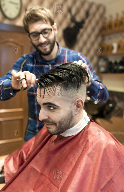Hairdresser cutting the sides of young man's hair in a barbershop