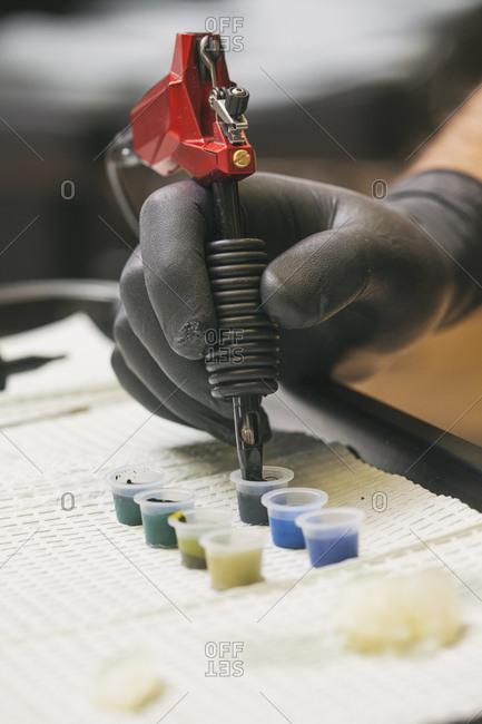 Tattooist's hand picking up tattoo ink with tattoo needle