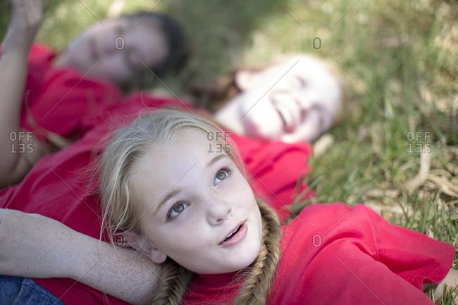 Girls lying on ground daydreaming