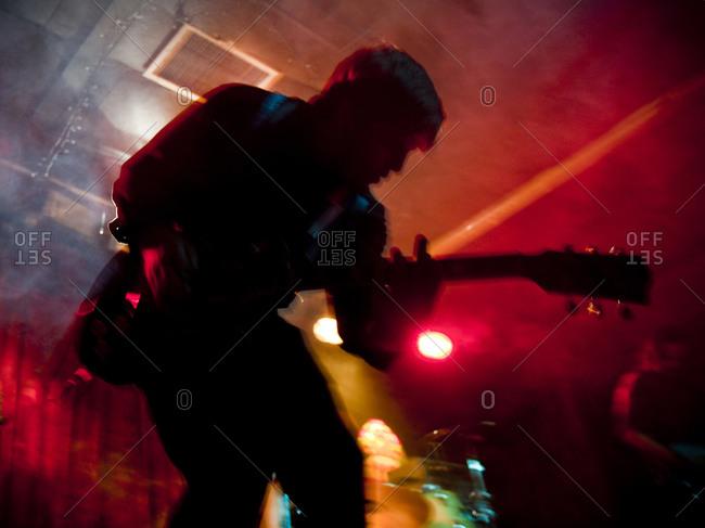 Young man playing electric guitar in nightclub