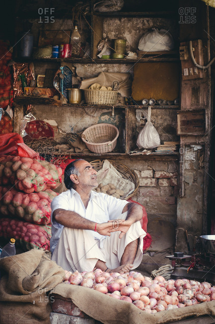 New Delhi, India - September 27, 2014: Vendor sitting next to vegetables at a market in New Delhi, India
