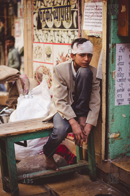 Jaisalmer, India - November 9, 2014: Wounded boy sitting on a street in Jaisalmer, Rajasthan, India